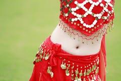 震动她的臀部的一套热的红色服装的肚皮舞表演者 库存照片