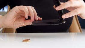 震动她的钱包和搜寻金钱的妇女慢动作英尺长度 掉下来在桌上的一枚硬币 股票录像