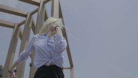震动臀部的华美的热情的青少年的白肤金发的妇女跳舞拉丁美州的样式外面与夏天天空和修造在背景中- 股票录像