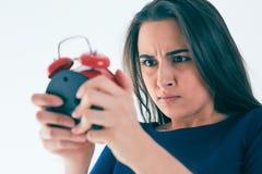 震惊和恼怒的妇女画象有闹钟的在白色背景 免版税图库摄影