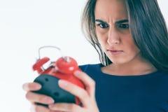 震惊和恼怒的妇女画象有闹钟的在白色背景 免版税库存照片