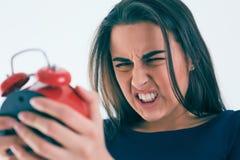 震惊和恼怒的妇女画象有闹钟的在白色背景 库存照片