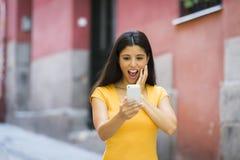震惊和惊奇的可爱的年轻拉丁妇女发短信和谈话在她巧妙的手机 皇族释放例证