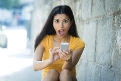 震惊和惊奇的可爱的年轻拉丁妇女发短信和谈话在她巧妙的手机 免版税库存照片