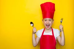 震惊和惊奇的女孩尖叫在拿着一把匙子和叉子在黄色背景的一位红色厨师的衣服与拷贝空间 库存图片