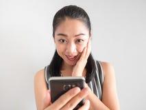 震惊和惊奇的妇女用途智能手机 免版税图库摄影