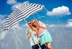 震惊夫妇在于多暴风雨的天气的伞下 库存图片