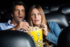 震惊夫妇观看的电影在剧院 免版税库存照片