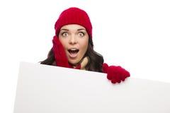 震惊女孩佩带的冬天帽子和手套举行空白的标志 图库摄影
