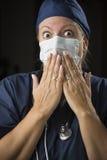 震惊女性医生用在嘴前面的手 免版税库存图片