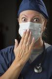 震惊女性医生用在嘴前面的手 免版税库存照片