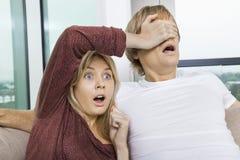震惊妇女覆盖物人的眼睛,当在家时看电视 免版税库存图片