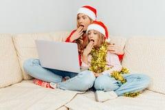 震惊妈妈和她的女儿,打扮在圣诞老人的帽子,使用一l 库存照片