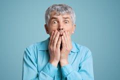 震惊害怕年长男性模型用手包括嘴,惊奇,并且惊吓听见可怕的新闻,能` t相信  免版税库存图片