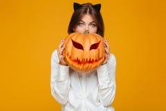 震惊少妇在疯狂的猫万圣夜服装穿戴了 免版税库存图片