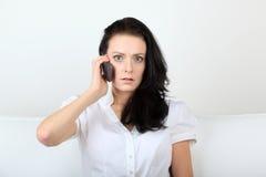 震惊少妇通过她的移动电话沟通与目光接触 免版税库存照片