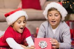 震惊打开礼物的兄弟和姐妹 免版税库存照片