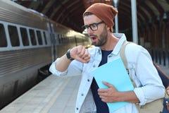 震惊男性在检查在火车站的时间以后 库存图片