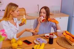 震惊的姐妹感觉看见妹妹吃含糖的食物 免版税库存照片