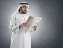 震惊的阿拉伯生意人报纸读取 图库摄影
