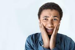 震惊非裔美国人的青少年的男孩画象用在看照相机的面颊的手 免版税库存图片