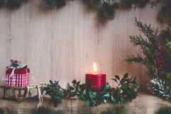 霍莉装饰的蜡烛和分支与圣诞节装饰品的在一个木制框架 免版税库存照片