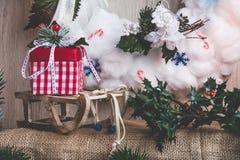 霍莉,雪撬,有一件礼物的一个箱子的分支在棉绒花圈的背景  库存图片
