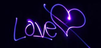霓虹心脏和题字在黑暗的背景爱 免版税库存照片