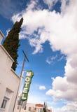 霓虹汽车旅馆标志明白蓝天白色滚滚向前的云彩 免版税库存图片