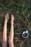 露出在草和耳机的女性腿 免版税库存照片