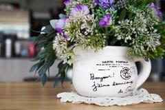 露天与花的咖啡店在木桌上的花瓶 免版税库存照片