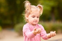 露天使用一件桃红色的礼服的美丽的小女孩 免版税库存图片