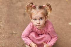 露天使用一件桃红色的礼服的美丽的小女孩 免版税图库摄影