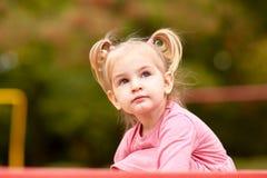 露天使用一件桃红色的礼服的美丽的小女孩 图库摄影