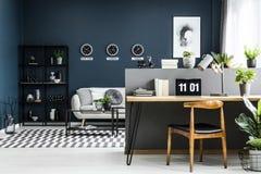 露天场所与书桌、椅子、植物和mod的家庭办公室内部 免版税库存照片