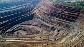 露天矿猎物鸟瞰图与许多的机械在工作 免版税库存照片