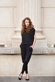 露背的连衫裤的时髦的女人 免版税图库摄影