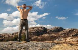 露胸部的人放松在山站立 免版税库存图片