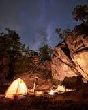 露营地在巨大的陡峭的岩层中的晚上 站立在旅游帐篷前面的妇女 免版税库存图片