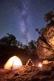 露营地在晚上 做运动亭亭玉立的女孩舒展体操锻炼在小旅游帐篷 库存图片