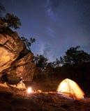 露营地夜 女孩坐在旅游帐篷前面的冰砾观看的篝火 免版税库存图片