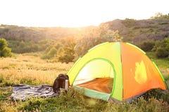 露营齿轮和游人帐篷在原野 免版税库存图片