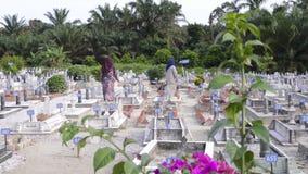 霹雳州,马来西亚,大约寻找他们的亲戚的坟墓的7月2015年-两回教妇女在一个大回教坟园在Ip镇  股票录像