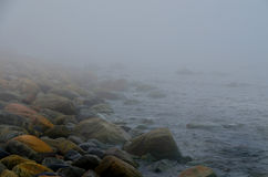阴霾和雾在一个多岩石的海滩 免版税库存照片