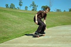 青少年下坡的溜冰者 免版税库存图片