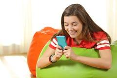 青少年使用一个蓝色巧妙的电话在家 图库摄影
