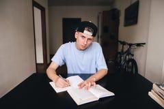 青少年做着家庭作业,当坐在他的屋子里时 看看照相机 免版税库存照片