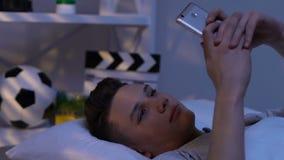 青少年发短信在智能手机,在床上,聊天与女朋友,约会站点 股票录像