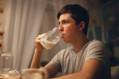 青少年在上床前喝牛奶在厨房里在晚上 免版税库存图片
