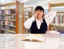 青少年在图书馆里注重和挫败的混合的族种学生 免版税库存照片
